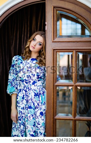 Portrait of a very beautiful sad girl with the blue dress on a background of doors - stock photo