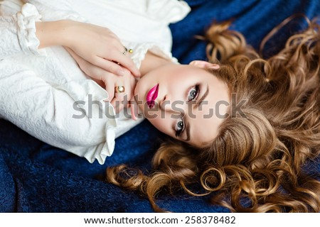 Portrait of a very beautiful sensual glamorous red-haired girl in a white blouse and a blue skirt lying on the floor in the Studio on a dark background, close up - stock photo