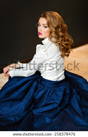 Portrait of a very beautiful sensual glamorous red-haired girl in a white blouse and blue skirt, sitting on the floor in the Studio on a dark background - stock photo