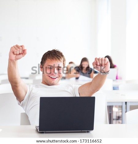 Portrait of a very happy young, male college student working on his laptop computer in a classroom/study room/library - expressing joy/success (shallow DOF; color toned image) - stock photo