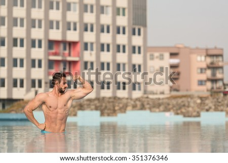 Portrait Of A Very Muscular Sexy Man In Underwear At Swimming Pool Showing Biceps - stock photo