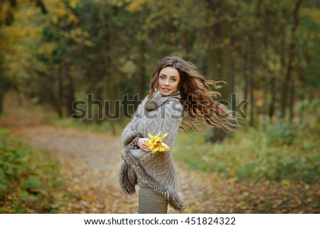 Portrait of a very pretty, smiling girl in a knit sweater, hair flying in the autumn in the park - stock photo