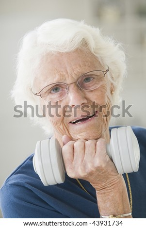 Portrait of a very senior woman exercising with a hand weight - stock photo