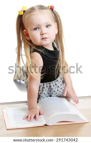 Portrait of a very serious little girl who is reading a book - isolated on white background - stock photo