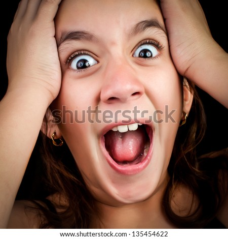 Portrait of a very surprised or scared girl screaming loudly with her hands on her head isolated on a black background - stock photo