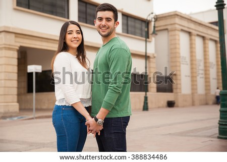 Portrait of a very young couple holding hands and making eye contact while hanging out in the city - stock photo