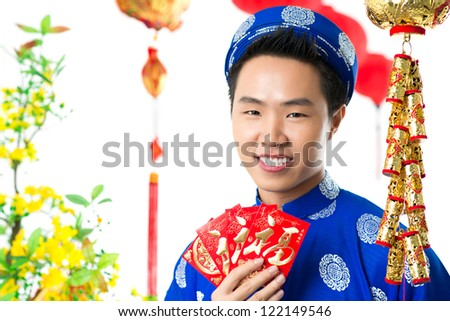 Portrait of a Vietnamese in traditional clothing with New Year envelopes - stock photo