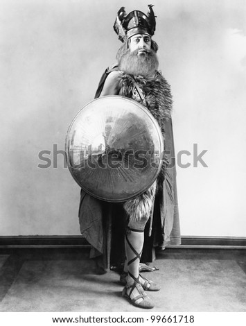 Portrait of a Viking warrior standing and holding a shield