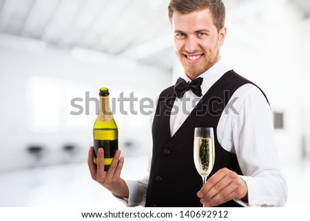 Portrait of a waiter holding a champagne glass