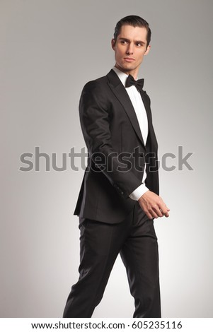 portrait of a walking young elegant man in tuxedo looking to side in studio