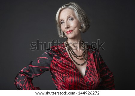 Portrait of a wealthy senior woman wearing necklace against black background - stock photo