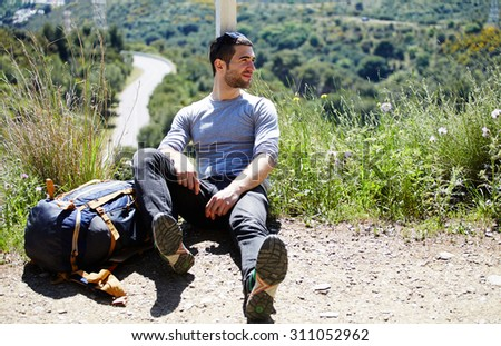 Portrait of a weary traveler taking break after active walk in mountains, male hiker enjoying landscape scenery while sitting on top hill with backpack and looks aside, tourist resting after hike way - stock photo