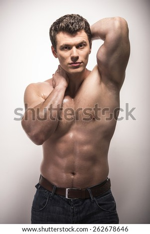 Portrait of a well built  muscular male model shirtless against white background.