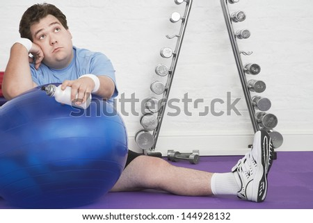 Portrait of a wistful overweight man sitting on floor with exercise ball in health club - stock photo