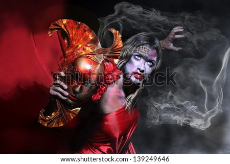 Portrait of a witch in a red dress holding in her hand a mask