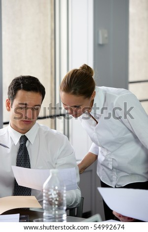 Portrait of a woman and man reading documents in an office - stock photo