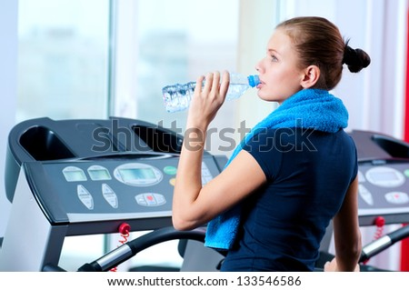 Portrait of a woman at the gym drinking water - stock photo