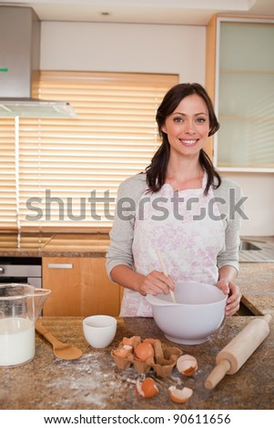 Portrait of a woman baking in her kitchen - stock photo