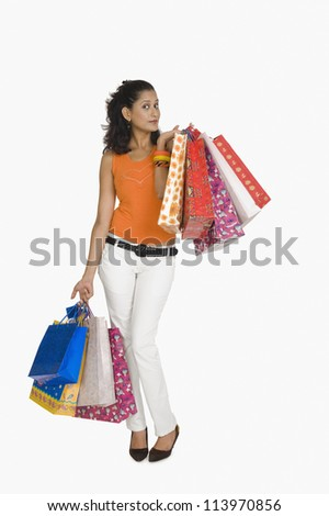 Portrait of a woman carrying shopping bags - stock photo