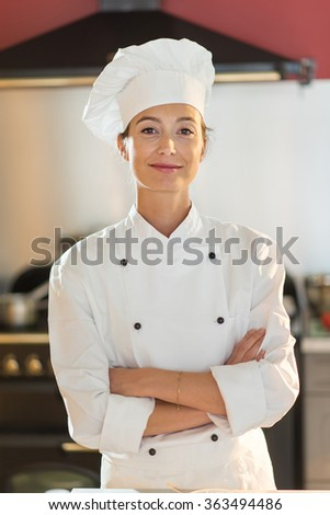 Portrait of a woman cook chef. She is looking at camera with confidence, standing in the kitchen arms crossed. She is wearing chef white clothes and hat. Blurred background.
