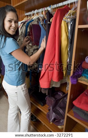 Portrait of a woman digging through her closet - stock photo