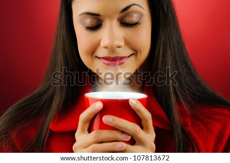 Portrait of a woman drinking a fresh cup of hot coffee with steam isolated on red background - stock photo