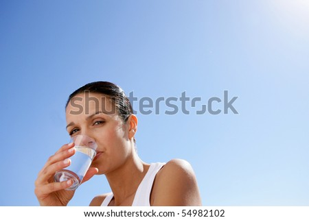 Portrait of a woman drinking a glass of water - stock photo