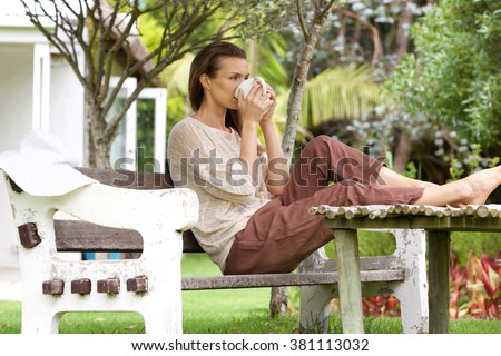 Portrait of a woman drinking tea outside in backyard - stock photo