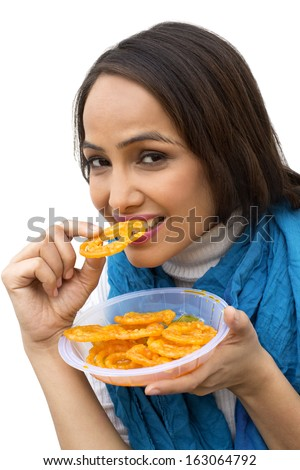 Portrait of a woman eating jalebi - stock photo