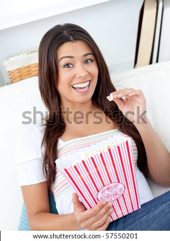Portrait of a woman eating pop corn on the sofa - stock photo