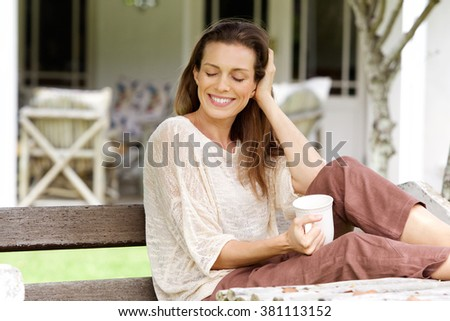 Portrait of a woman enjoying cup of coffee at home garden - stock photo