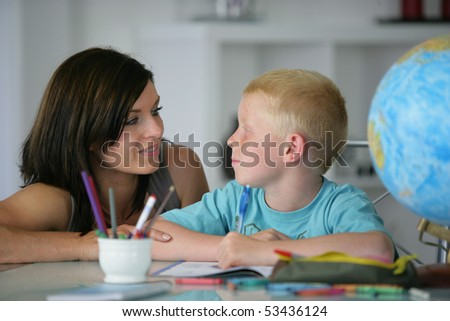 Portrait of a woman helping a boy to do homework - stock photo