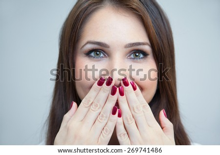 portrait of a woman hiding her mouth with hands - stock photo