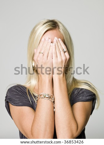 Portrait of a woman hiding in her hands - stock photo