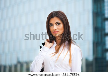 Portrait of a woman holding a jacket on her shoulder - stock photo