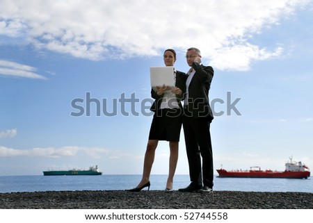 Portrait of a woman holding a laptop computer and a man with a phone - stock photo