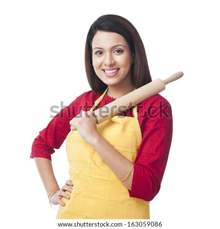 Portrait of a woman holding a rolling pin and smiling - stock photo