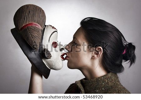 Portrait of a woman holding a traditional African mask and kissing it. - stock photo