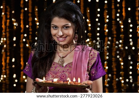 Portrait of a woman holding a tray of diyas - stock photo