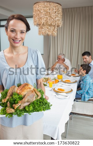 Portrait of a woman holding chicken roast with family at dining table in the house - stock photo