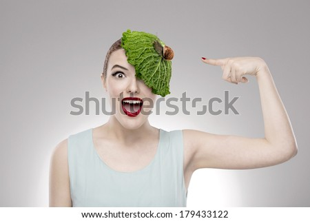 Portrait of a woman illustrating a vegan concept with a cabbage on the head with a snail on it