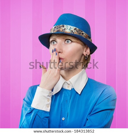 Portrait of a woman in a blue hat covering the mouth with her hand, pink stripy background - stock photo