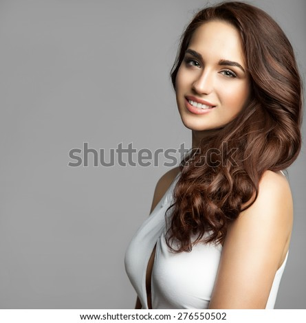 Portrait of a woman in a white dress with a long thick curly hair on gray background isolatad - stock photo