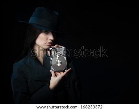 Portrait of a woman in black hat with a hard disk drive in her hands on dark background - stock photo