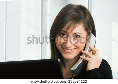 Portrait of a woman in front of her monitor while talking on the phone - stock photo