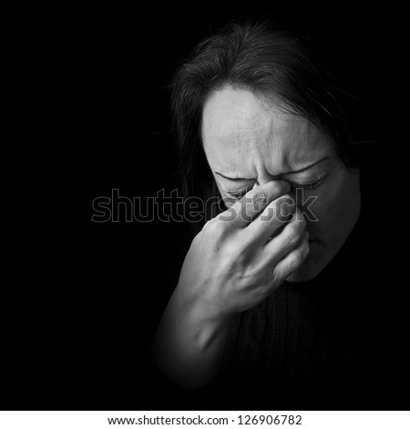 portrait of a woman in pain, frowning with hand on head with black background and copy space - stock photo