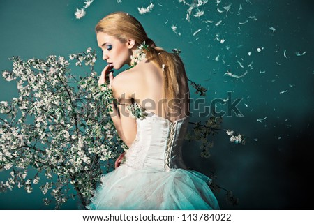 Portrait of a woman in wedding dress behind the branches with flowers - stock photo