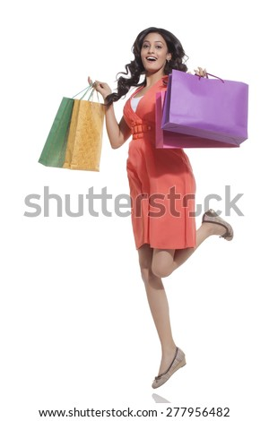 Portrait of a woman jumping with shopping bags