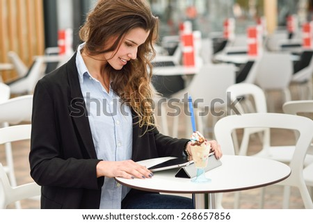 Portrait of a woman looking at her tablet computer, smiling and sitting in a coffee shop - stock photo