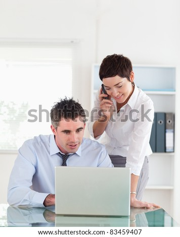 Portrait of a woman making a phone call while her colleague is looking at a laptop in an office